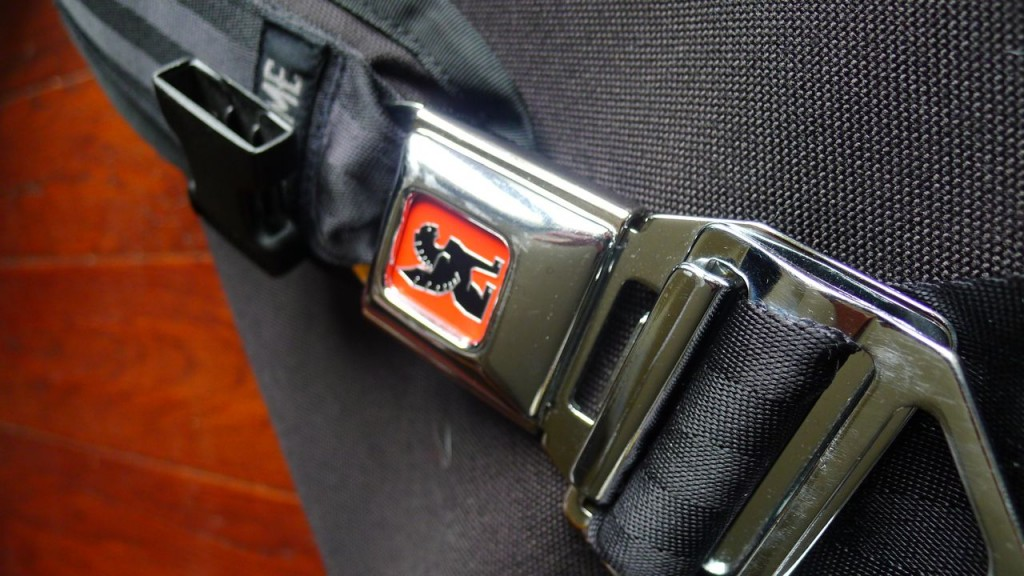 The stylish and secure seatbelt buckle strap closure on chrome bag